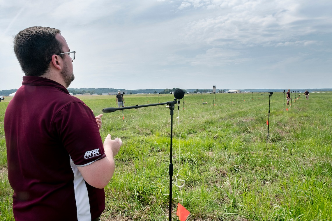 Engineers conducting acoustic tests in grassy field near runway.